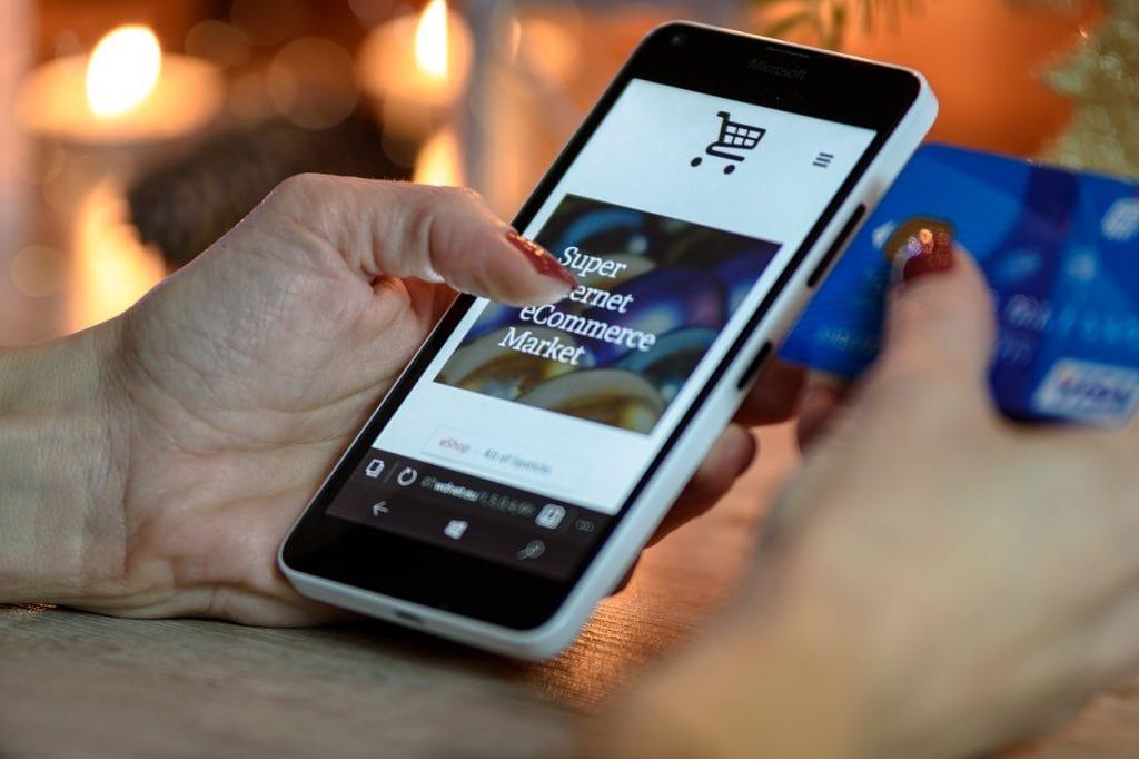 Czas uwierzytelnić transakcje na Amazon.pl. Mija deadline dla nowych sprzedawców zabawek - kobieta trzyma w ręce telefon i kartę kredytową.
