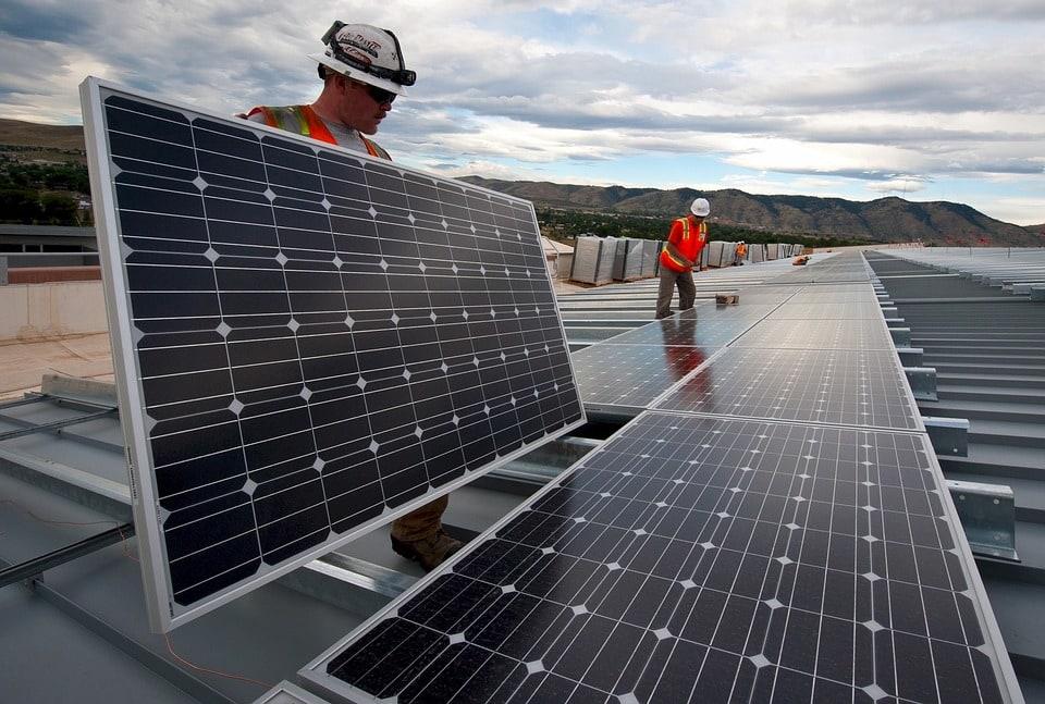 Sklepy Dino zasilane energią ze słońca - dwóch mężczyzn ana dachu instaluje panele słoneczne