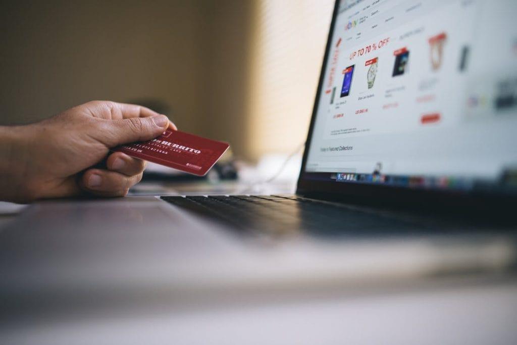 Trwa cyfryzacja płatności. To szansa na rozwój gospodarki - laptop stoi na biurku a męska dłoń trzyma kartę kredytową.