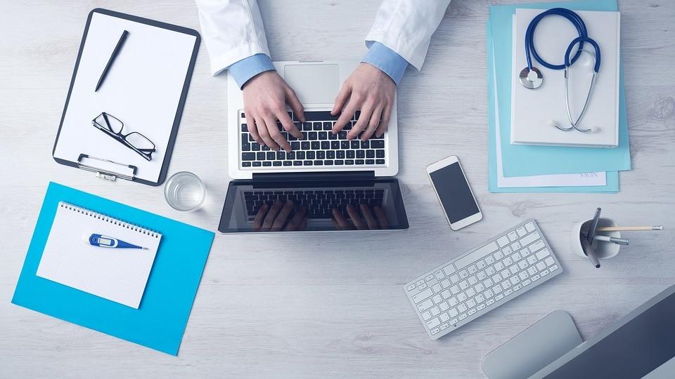 Cyfryzacja to przyszłość systemu ochrony zdrowia - mężczyzna, lekarz pisze na klawiaturze laptopa, na biurku leży telefon i notatnik.