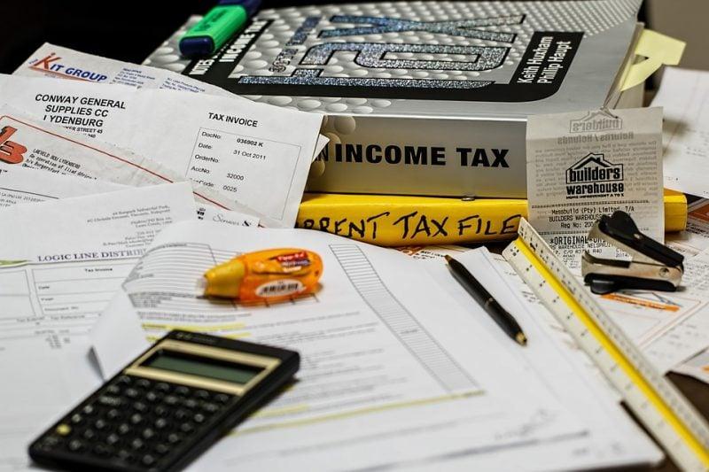 Najważniejsze rozwiązania podatkowe - dokumenty, książki,l kalkulator i długopis leża na biurku