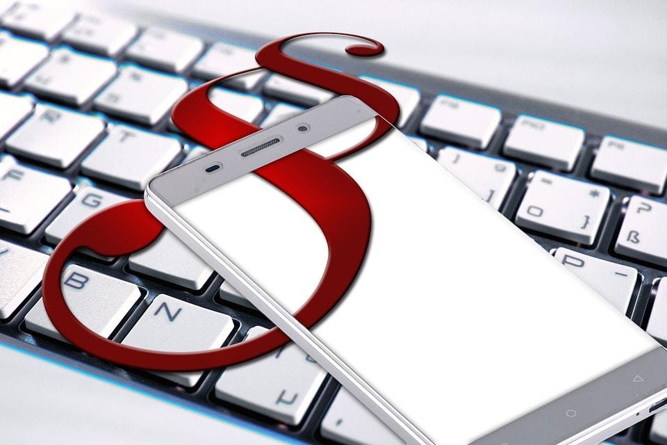 Działy prawne inwestują w narzędzia cyfrowe -telefon lezy na klawiaturze komputera.