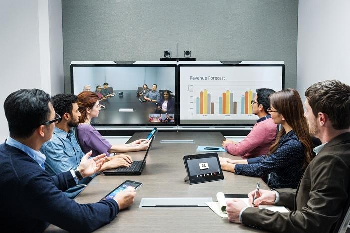 7 trendów pracy hybrydowej od Microsoft - telekonferencja, ludzie siedzą w biurze przy biurku na przeciwko telebimów