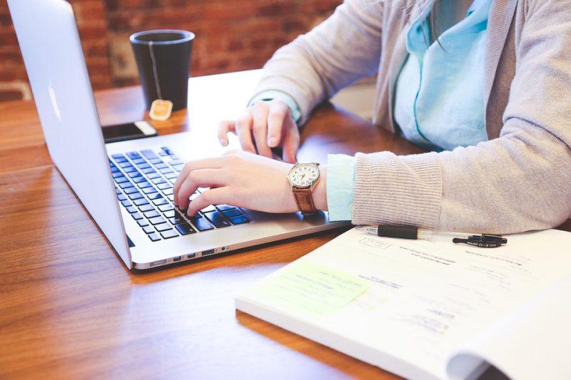 Bezrobocie w marcu 2021 roku - kobieta siedzi przy biurku i pisze na klawiaturze laptopa.