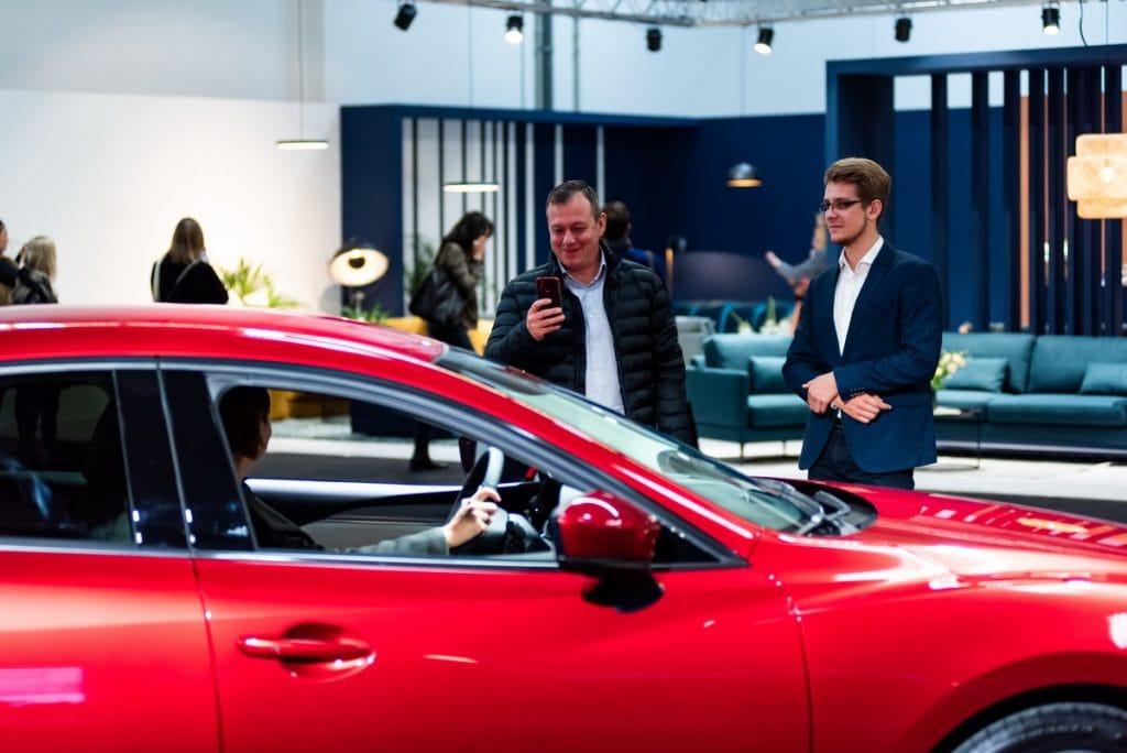 Limitowana edycja Mazdy dla patronów Radia 357 - ludzie oglądają czerwone auto w salonie
