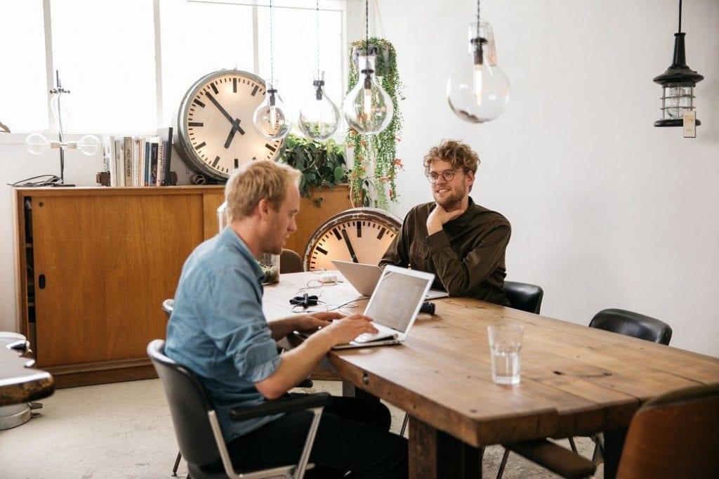 Sklepy internetowe rosną jak grzyby po deszczu -dwóch mężczyzn siedzi przy biurku przed otwartymi laptopami