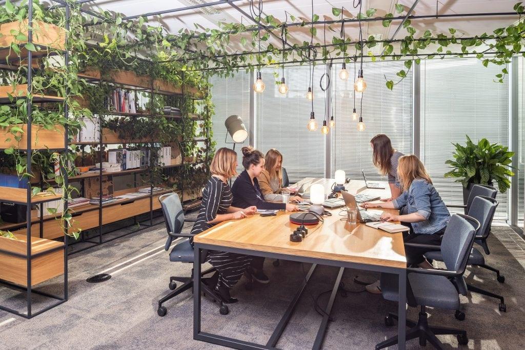 Jak pandemia wpłynęła na rozwój zawodowy kobiet ? - kobiety siedzą w biurze przy jednym dużym stole.