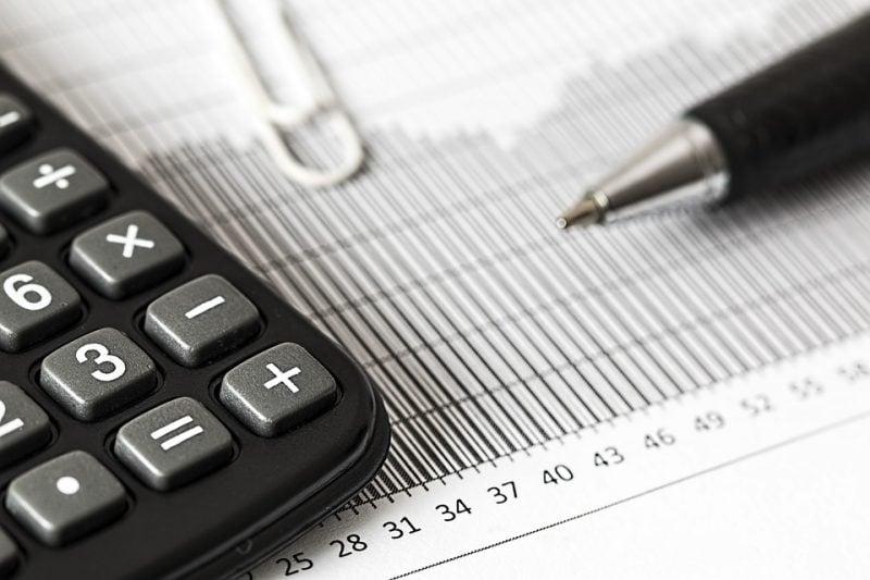 Nowe zasady wypełniania JPK_VAT z deklaracją (JPK_V7M, JPK_V7K)  - kalkulator, umowa i długopis leżą na stole.