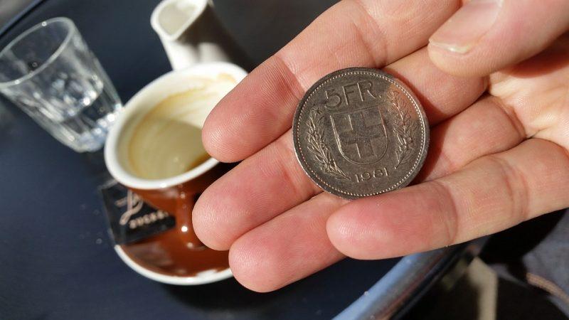 koszty odfrankowienia  - moneta chf na dłoni