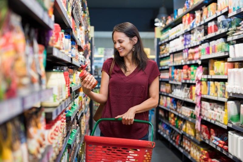 Komu ufają polscy konsumenci?- kobieta na zakupach w sklepie z koszykiem w reku czyta etykiety na opakowaniu produktu.