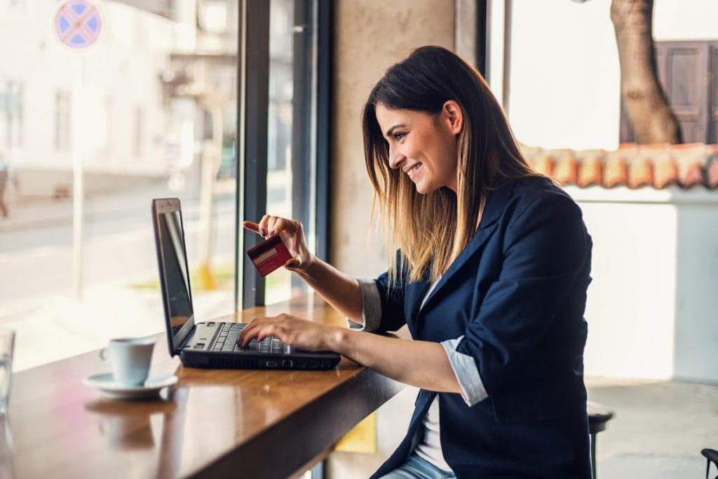 E-sklep, czyli sprzedaż online w czasach zarazy -kobieta siedząca przy stole, robi zakupy przez internet, płacąc karta kredytową