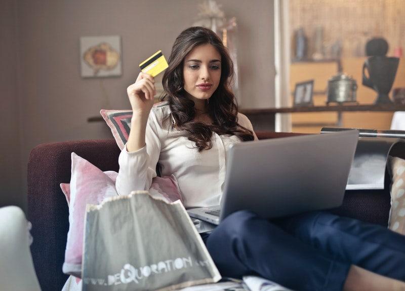 Dlaczego marki tracą klientów? Analiza rynku elektroniki - kobieta siedzi na kanapie z karta płatnicza w reku i laptopem na kolanach.