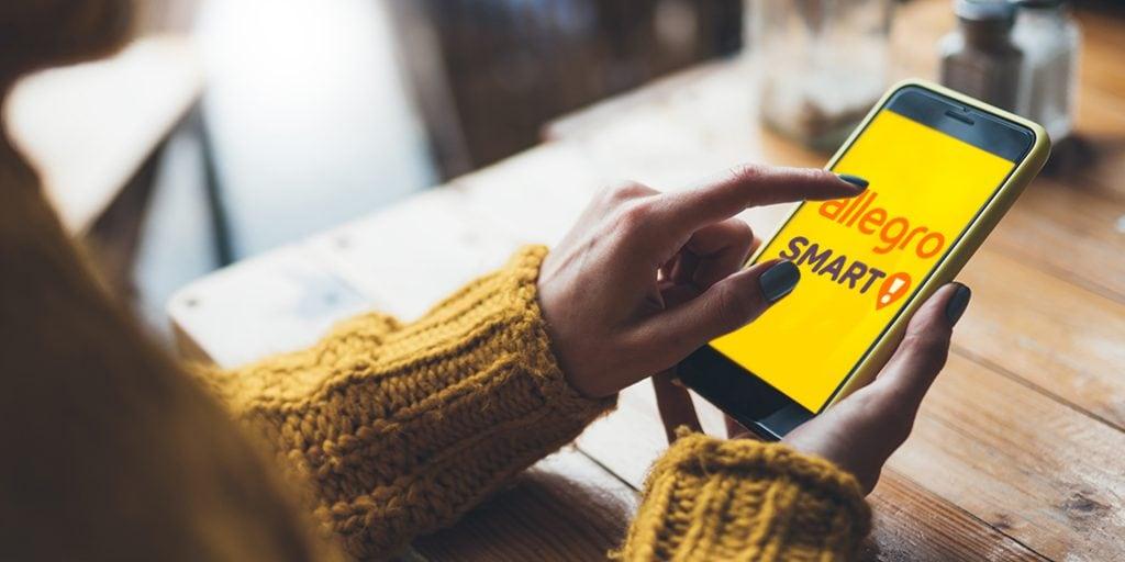 Allegro Biznes zadebiutuje w lutym - kobieta w żółtym swetrze trzyma w reku telefon.
