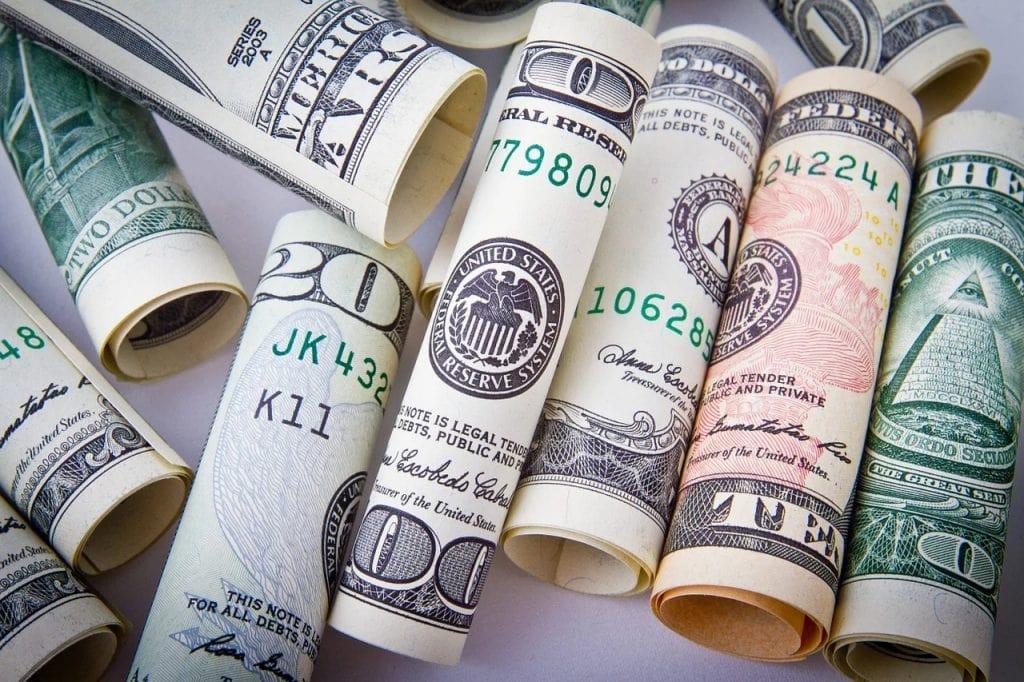 USA otwierają granice. Co z kursem dolara? - banknoty dolarowe zwinięte w rulon.