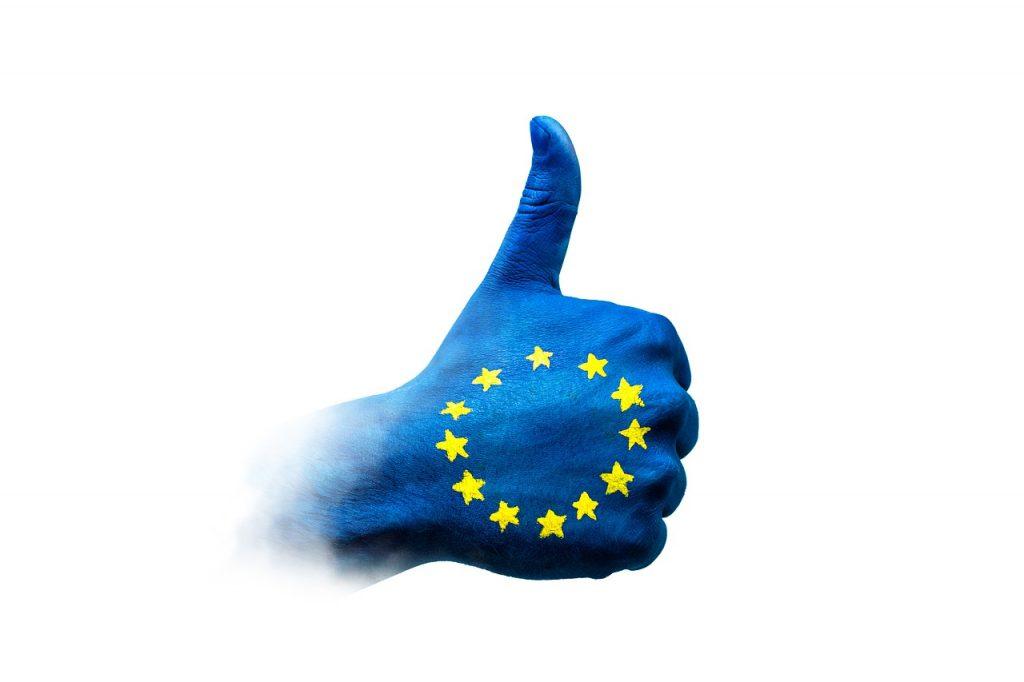 Koronawirus atakuje, a Europa wspiera obywateli - dłoń z kciukiem do góry pomalowana na niebiesko z flaga Unii Europejskiej