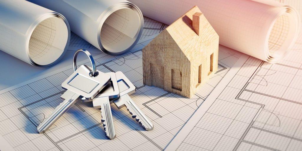 Rodzaje umów zawieranych z deweloperem - plany budowlane, klucze i mały drewniany domek.
