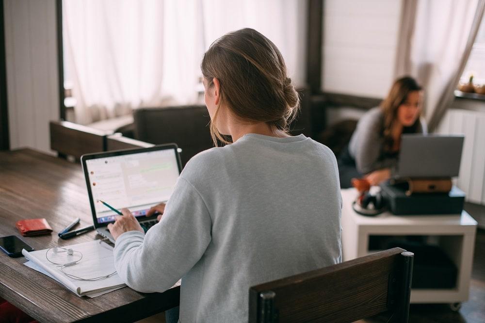 Pracownicy chcą zostać na home office   - kobiety siedza przed otwartymi laptopami i piszą na klawiaturze