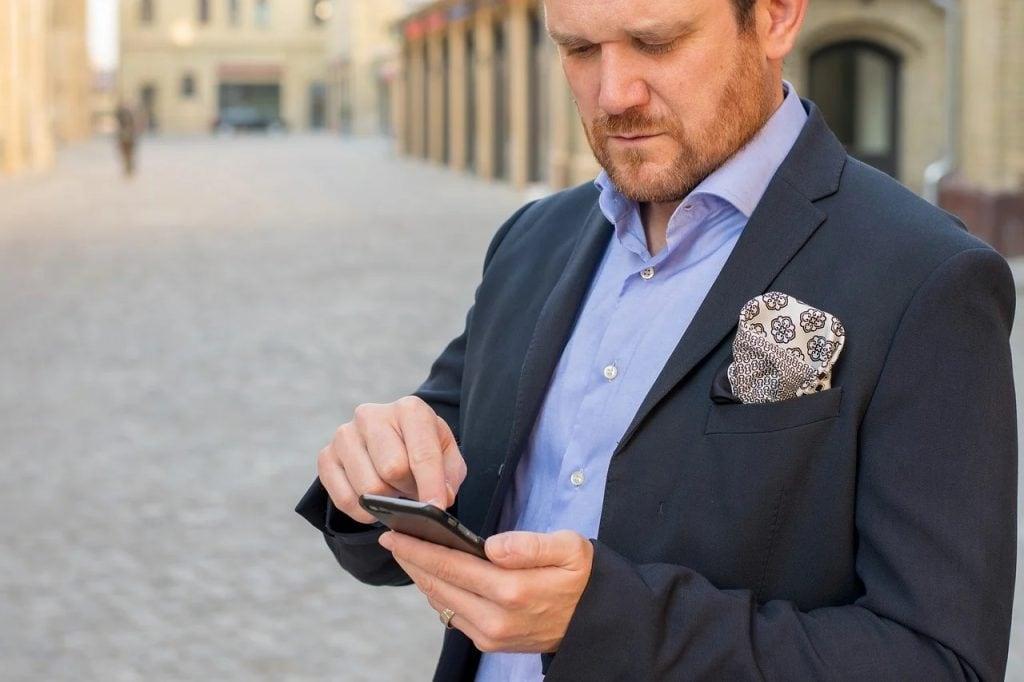 95% firm odczuwa boleśnie negatywne skutki pandemii - mężczyzna w garniturze w telefonem w ręku