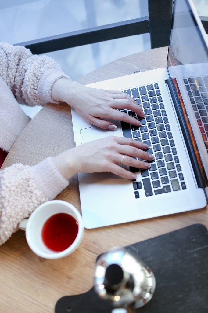 Millenialsi nie chcą wracać do biur, młodsi i starsi już chętniej - kobiece dłonie na klawiaturze laptopa.