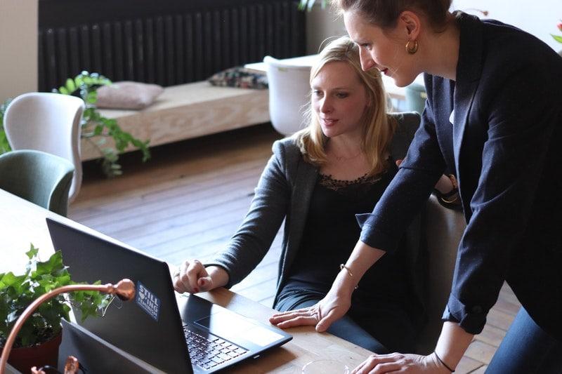E-faktura wchodzi w życie, czyli co musi wiedzieć przedsiębiorca- dwie kobiety patrzą w ekran laptopa.