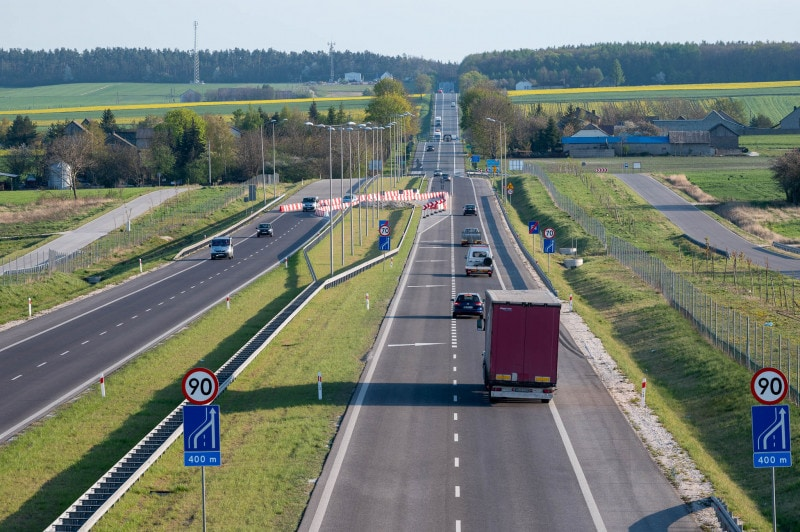 Przewóz pieniędzy przez granice - nowe przepisy unijne - auta  osobowe i ciężarowe jadą po drodze.
