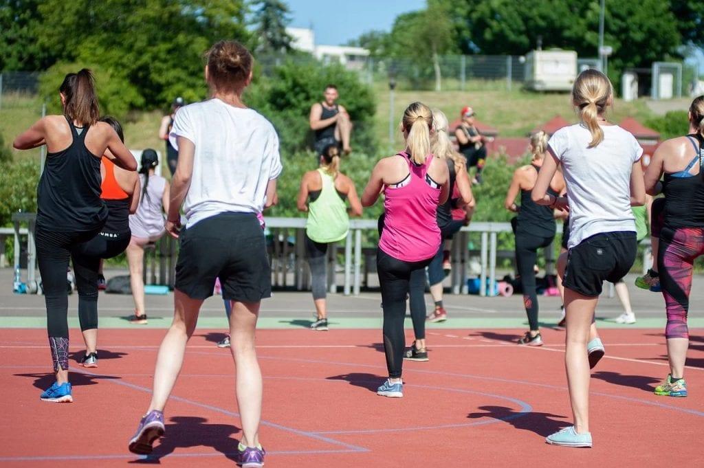 Branża sportowa rośnie - INTERSPORT notuje rekordową sprzedaż - ludzie w grupie ćwiczą na świeżym powietrzu.