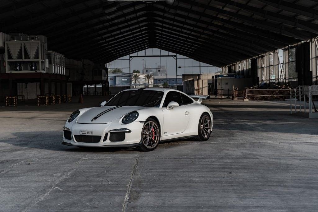 Porsche Digital wykorzystuje sztuczną inteligencję do wykrywania hałasu - białe auto Porsche zaparkowane przed fabryką.