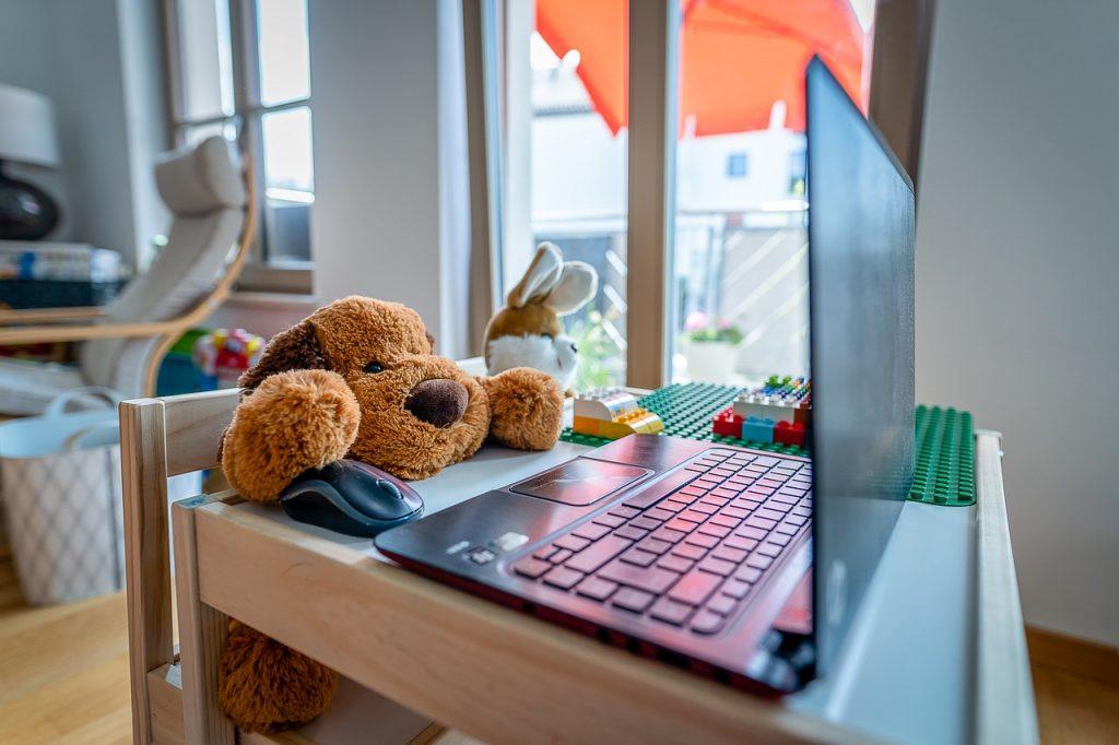 Kariera kobiet pod znakiem zapytania - miś zabawka siedzi na krześle w pokoju przed otwartym laptopem