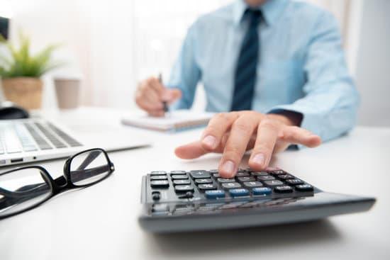 Koniec rajów podatkowych - nadchodzi wielka reforma międzynarodowego opodatkowania - mężczyzna liczy na kalkulatorze.