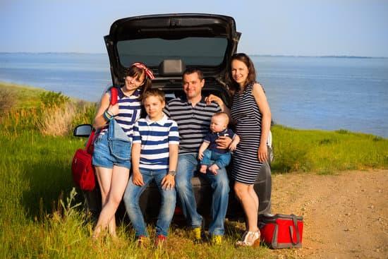 Polaków podróże małe i duże w 2021 roku - rodzina z dziećmi siedzi na tyle otwartego samochodu.