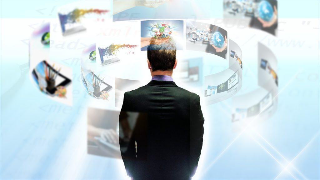 Pilnowanie dowodu osobistego nie zagwarantuje bezpieczeństwa danych osobowych - mężczyzna stoi tyłem do ekranów telewizyjnych.