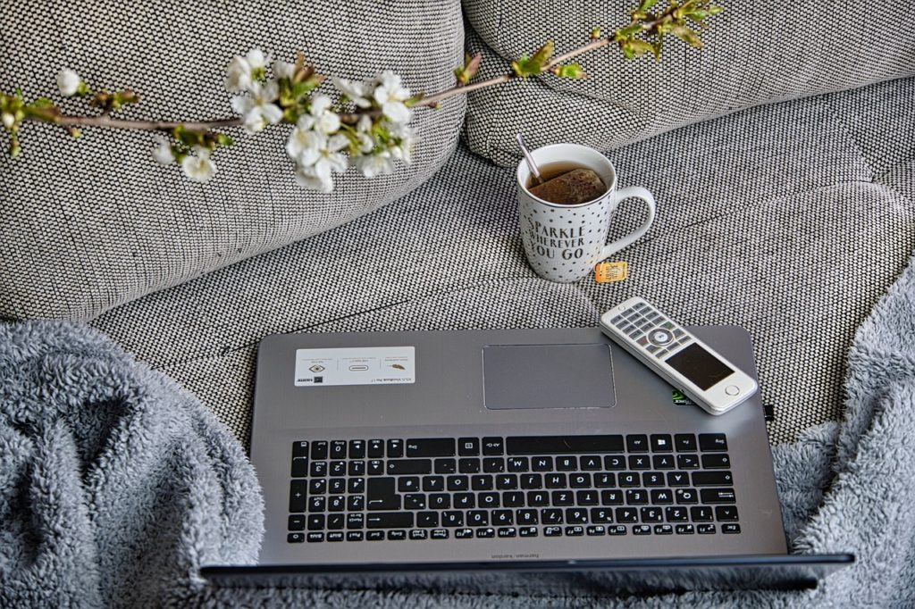MŚP powoli przekonuje się do pracy zdalnej - laptop i telefon leża na kanapie obok kubka z herbatą.