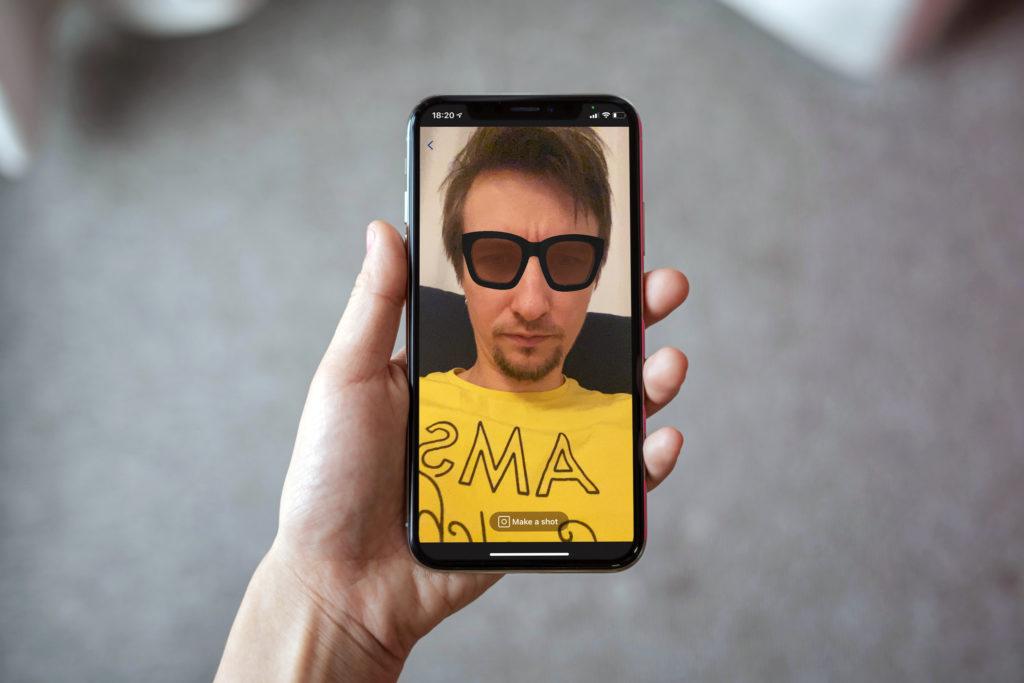 """""""Własny biznes to mój styl życia. Motywuje mnie, żeby ciągle się dokształcać i śledzić wszystkie nowe pomysły i rozwiązania""""- Anton Bulakh- męska dłoń trzyma telefon"""