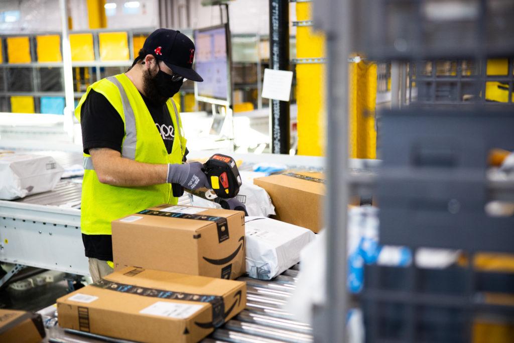 Amazon kontra Allegro – kto skorzysta na starciu gigantów? - mężczyna pakuje paczki w magazynie