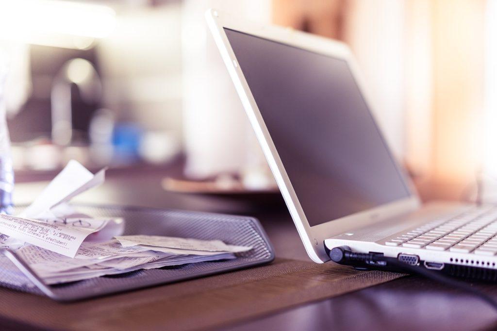 EFL sadzi las. Drzewo za e-fakturę - biurko z laptopem, obok faktury i rachunki.