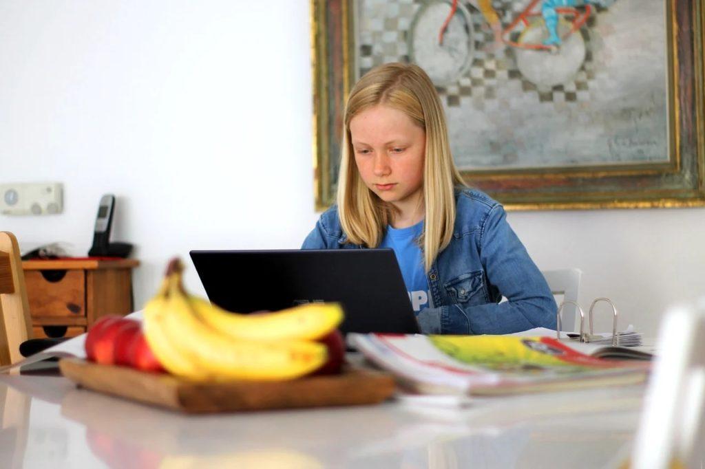 Pandemia to… reforma oświaty. Wykorzystajmy to! - dziewczynka siedzi przy stole przed otwartym laptopem.