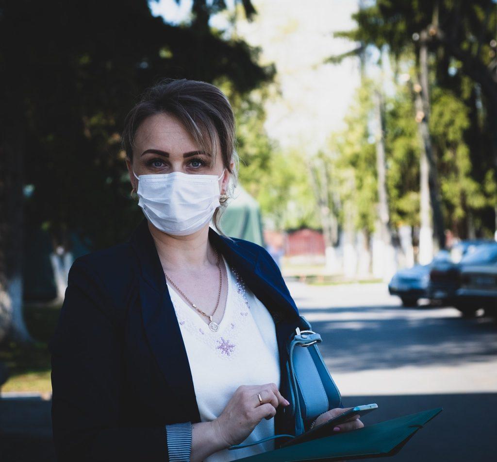 COVID-19 blokuje rozwój małych miast - kobieta  w masce z telefonem i dokumentami w ręku.