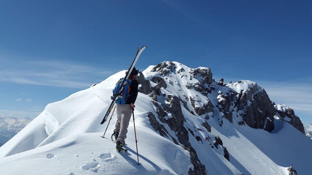 Branża turystyczna tonie w długach przez zimowy lockdown - mężczyzna w górach zasypanych śniegiem z plecakiem i nartami na plecach.