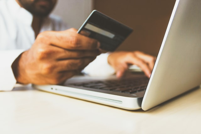 E-commerce rośnie jak nigdy wcześniej - mężczyzna siedzi przed otwartym laptopem z karta kredytowa w ręku.