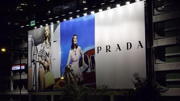 Marki luksusowe inwestują w zrównoważony rozwój i cyfryzację - bilbord Prady z modelkami na zdjęciach.