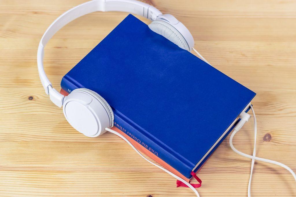 Audiobooki, e-booki i podcasty w 2020 roku - książka słuchawki leżą na biurku.