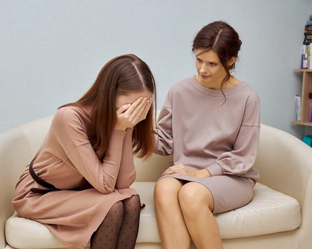 Wsparcie psychologiczne - nowy benefit usług pozapłacowych - dwie kobiety siedzą na kanapie, jedna z nich chowa twarz w rękach .