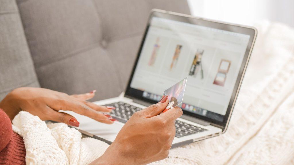 Nowe trendy e-commerce - kobieta siedzi na kanapie przed otwartym laptopem i trzyma kartę kredytową w ręku.