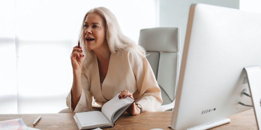 Kobiety doskonale wiedzą, czego chcą w sferze zawodowej - kobieta siedzi przy biurku przez ekranem komputera.