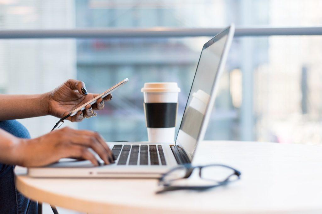Wniosek o kredyt hipoteczny on-line - kobieta pisze na klawiaturze laptopa, w drugiej ręce trzyma telefon.