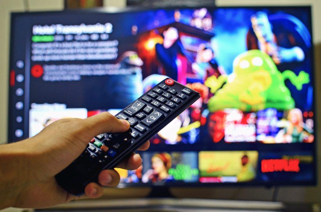 Podatek medialny objawem starej choroby  - męska dłoń trzyma pilot w ręku na tle telewizora.