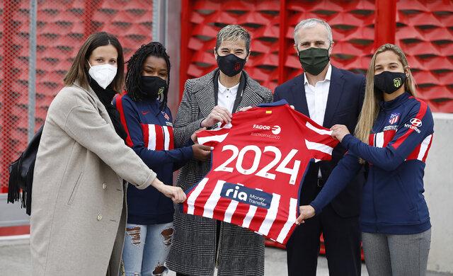 Grupa AMICA sponsorem Atletico Madryt - kobiety i mężczyzni trzymają razem jedna koszulkę drużyny piłkarskiej.