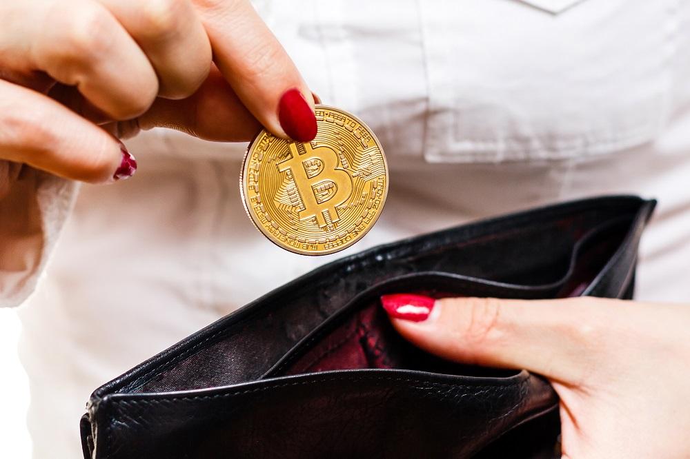 Jogurt i opony kupione za Bitcoiny: przyszłość płatności w e-commerce? - kobieta wkłada do portfela monetę bitcoina.