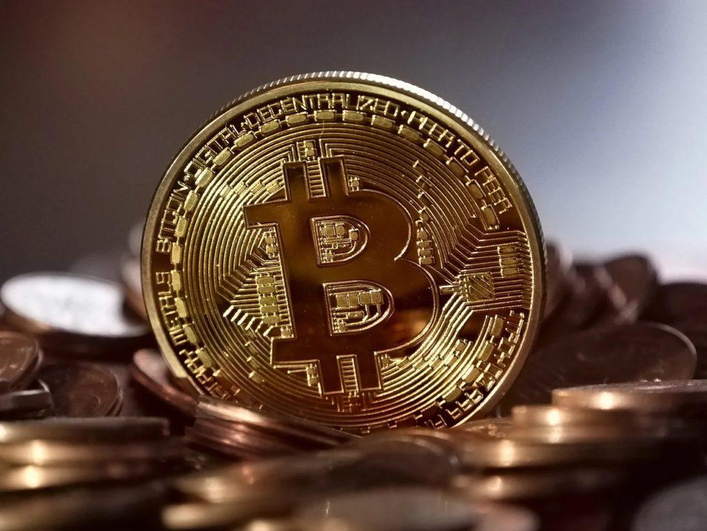 Popyt na kryptowaluty nie maleje - złota moneta na tle innych monet.