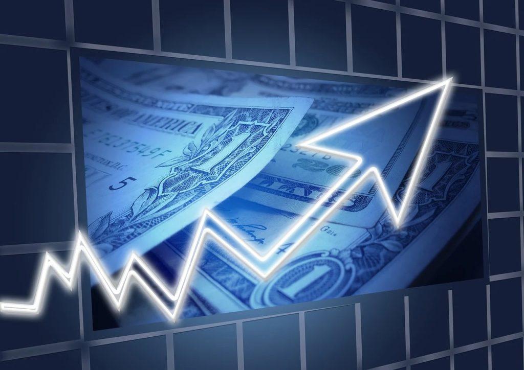 Tydzień z Rezerwą Federalną i raportami spółek - wykres, strzałka i banknoty dolarowe w tle